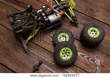 Dismantled broken Rc radio control car crawler model toy repair. Green toy suv in repairshop workplace, top view. Wheels on foreground