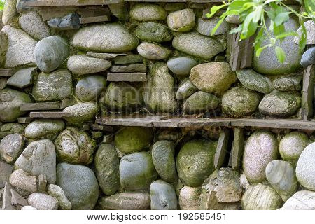 Natural stone landscaping in home garden. Stone wall background.