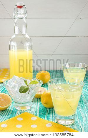 lemonade or limoncello in a yoke stopper bottle drink in glasses sherbet glass with ice cubes decorated by mint leaf on turquoise colored wooden table with yellow napkin at white polka dots.