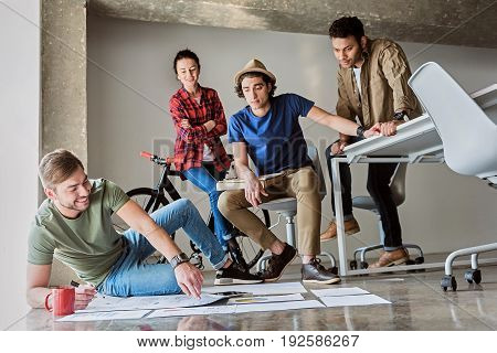 Low angle of cheerful start-up team planning new project together. Guy is sitting on floor and pointing finger at graphic