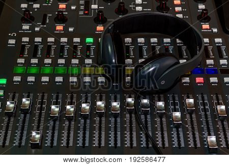 The audio equipment, control panel of digital studio mixer and headphones, close-up.