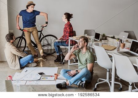 Working process. Happy creative team is discussing new project. Guy is standing and leaning on bicycle. His colleague is talking on cellphone while sitting on floor