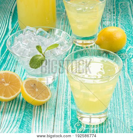 lemonade or limonchello in glasses glasses with ice cubes sherbet glass with ice cubes decorated by mint leaf lemon fruits on turquoise colored wooden table with yellow napkin at white polka dots