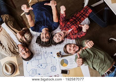 We are great team. Joyful young man and woman showing okay sign while lying on floor near papers. They are looking at camera and smiling. Top view