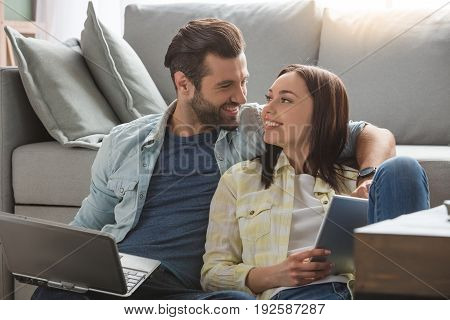 Young woman and man family couple indoors using laptop
