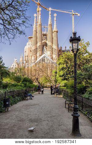BARCELONA SPAIN - APRIL 20: City tour bus in front of Basilica Sagrada familia designed by Antoni Gaudi on April 20 2017 in Barcelona