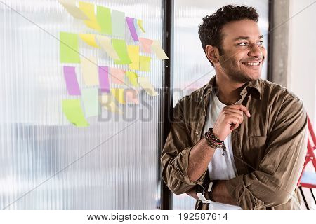 Pensive young male freelancer creating new ideas. He is standing near colorful papers on glass wall. Guy is looking aside and laughing. Portrait