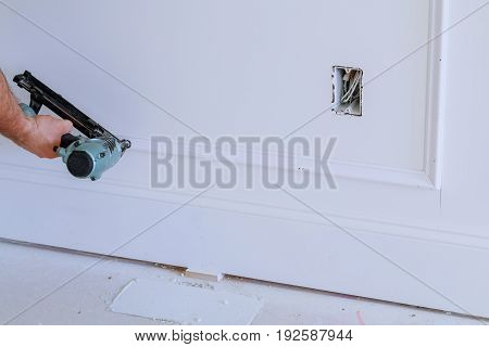 Do It Yourself Home Owner Repairing Frame Molding With Nail Gun,