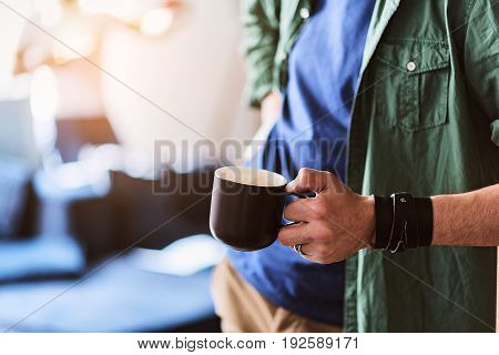 Close up of male hand holding cup of coffee. Guy is standing with relaxation. Copy space in left side