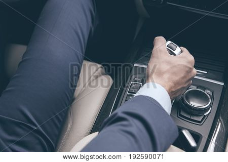 Young business person test drive new vehicle gear shift