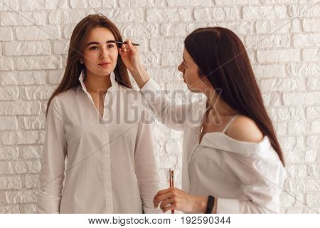 Woman client and beautician completes the correction of eyebrows. Visagiste applying eyebrow makeup.