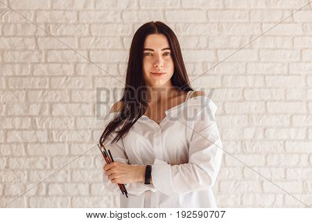 Cosmetologist with tassels for eyebrow correction posing on camera on white background.