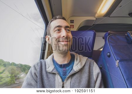 Young Man Traveling On A Train And Smiling At Someone