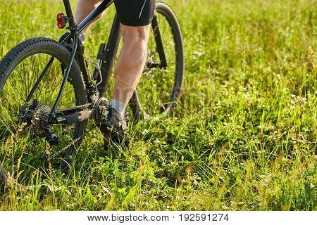 Close-up of cyclist man legs riding mountain bike on the green meadow. Detail of the cyclist and mountain bike. Sportive shorts and sportive shoes. Extreme travel in the countryside. Concept of the healthy lifestyle.