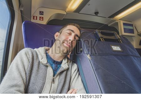Young Man Traveling On A Train And Sleep On Blue Suitcase Next To Him