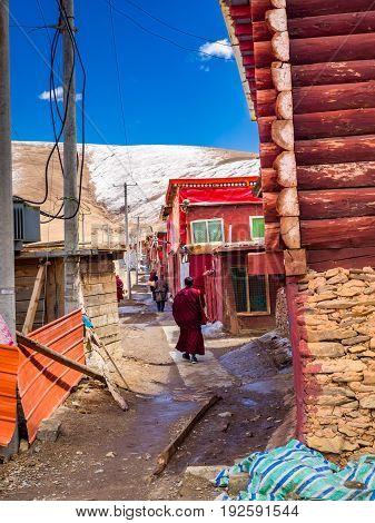 Tibetan buddhist monks walking in a nerrow street at Yarchen Gar Monastery in Sichuan China