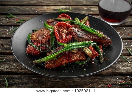 Grilled beef with vegetables, spring onion, asparagus on plate