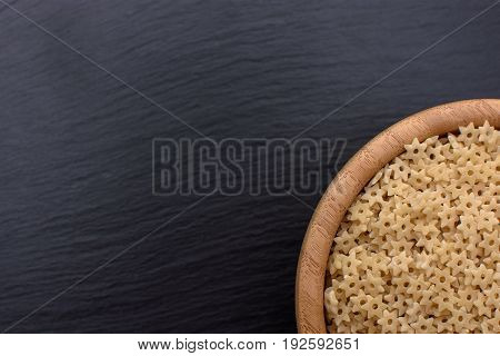 Macaroni In The Form Of Asterisks Lie In A Wooden Cup On A Black Stone Board, Space For Text