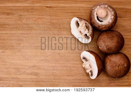 Gray Mushrooms Champignons Lie On A Wooden Kitchen Board