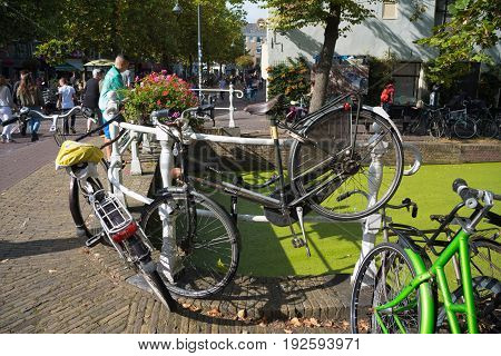 DELFT NETHERLANDS - SEPTEMBER 18 2016: Various bicycles parked on a small bridge in the center of Delft