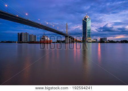 Sunset scence of Bangkok Panorama View of Rama 9 bridge in Bangkok city with sunset sky and clouds at Bangkok Thailand. And Reflection on river