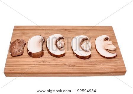White Mushrooms Champignons Sliced Thin Slices On A Wooden Cutting Board, Isolated On A White Backgr