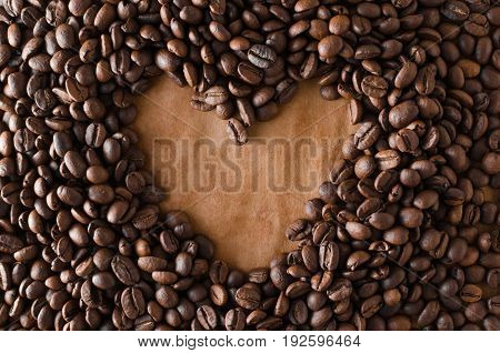 Coffee beans on old paper in the form of a heart closeup