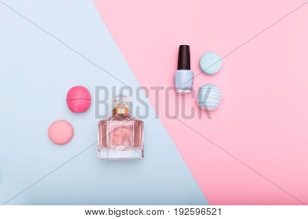 cosmetics and macarons on blue and pink background
