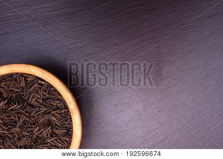 Black Rice Lies In A Wooden Plate On A Black Stone Slate Board With Space For Text