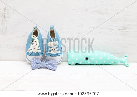 Toy whale bow tie and children's blue shoes for a boy on a white wooden background