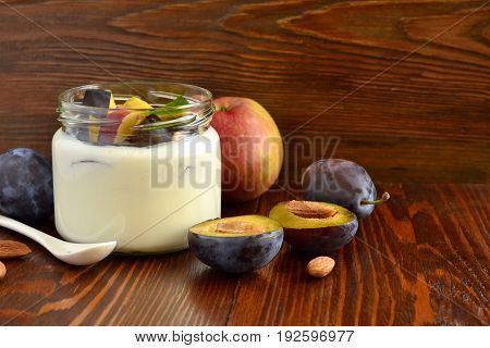 Homemade yogurt in small jars with berries fruits almonds
