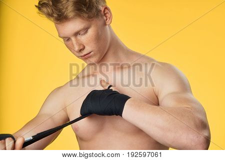 Athlete, red hair, elastic bandage, guy on a yellow background, fitness, sports.