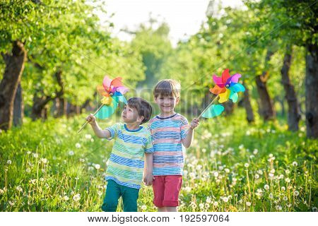 Two Happy Children Playing In Garden With Windmill