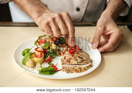 Mature male professional chef cooking meal indoors decorating