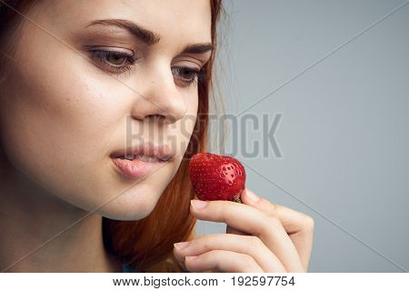 A girl holds a strawberry and bites her lip, a beautiful woman on a gray background, sweetness, fruit, food, berries.