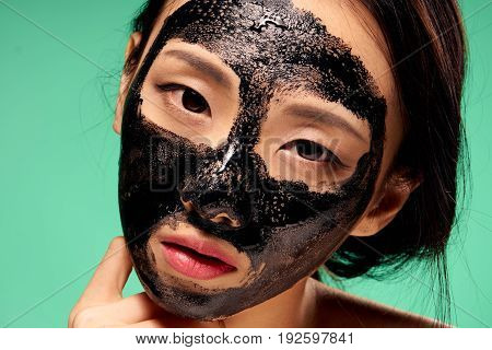 Asian, woman on a green background, black coal cosmetic face mask, beauty, health.