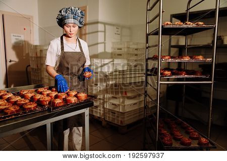 Baker smiling at camera holding rack of rolls in a commercial kitchen