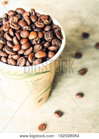 Coffee beans in a cup on a wooden table, selective focus