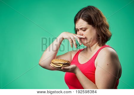 Diet, fat, a woman on a green background holds a hamburger, fast food, improper food.