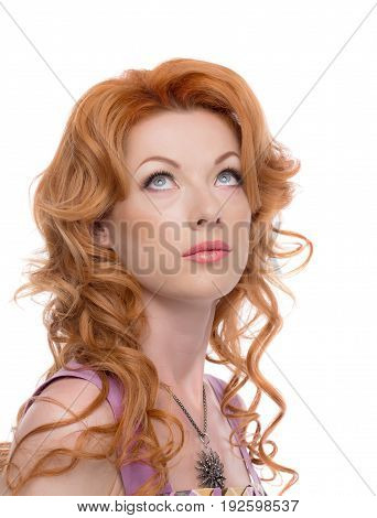 Headshot of a redhead lady looking upwards wearing a silver necklace and a pink dress.