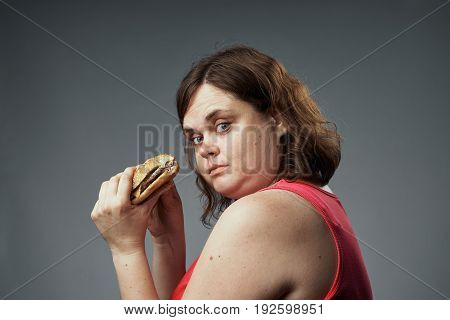 Fat, woman on a gray background holds a hamburger, fast food, diet, health, beauty.