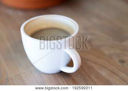 Cup of hot coffee and candies, standing on wooden table