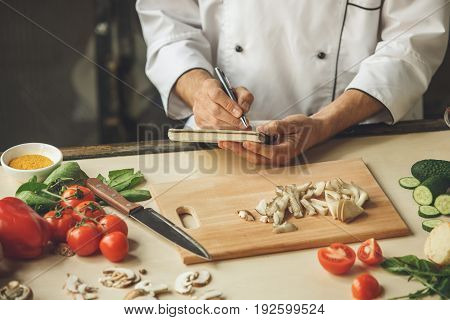 Mature male professional chef cooking meal indoors writing receipt