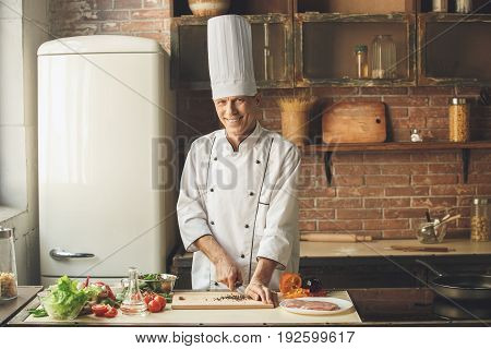 Mature male professional chef cooking meal indoors cutting ingredients