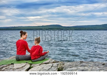 Rear view of the mother and daughter are practicing yoga on the rock near river. Beautiful young mother and little daughter in the sportwear and barefoot sitting on the green yoga mat. Beautiful river landscape. Concept of the healthy lifestyle.