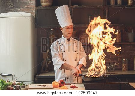 Mature male professional chef cooking meal indoors frying