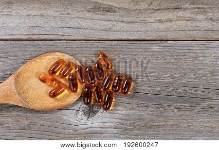 Pacific salmon fish oil capsules and wooden spoon on rustic wood. Flat lay view.