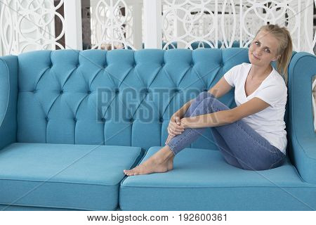 Young caucasian woman sitting on blue sofa