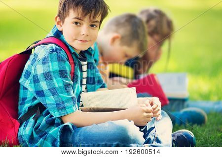 Children with rucksacks sitting in the park near school. Pupils with books and backpacks outdoors