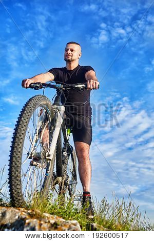 Bottom view of young cyclist standing with bike on rocks against blue sky. Beautiful sportsman in the black sportwear and with sportive shoes. Vertical photo. Beautiful sky with clouds like a background. Concept of the healthy lifestyle.